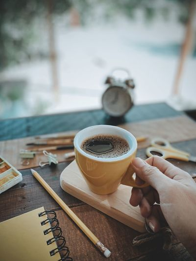 Cropped image of hand holding coffee cup on table