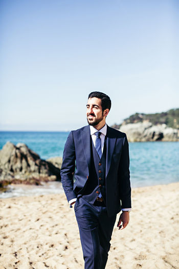 Smiling bridegroom looking away while walking at beach against clear sky during sunny day