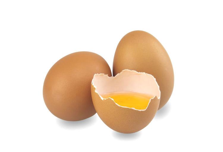 Close-up of broken egg against white background