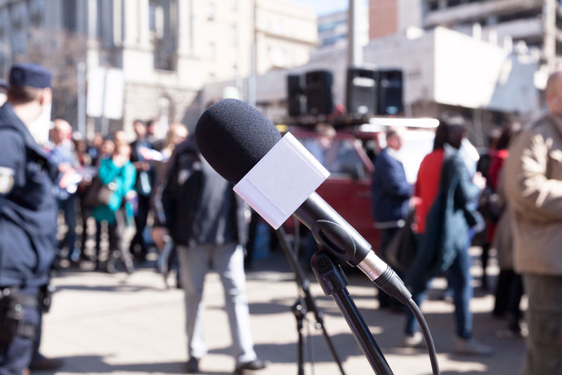 Close-up of microphone with people in background on street