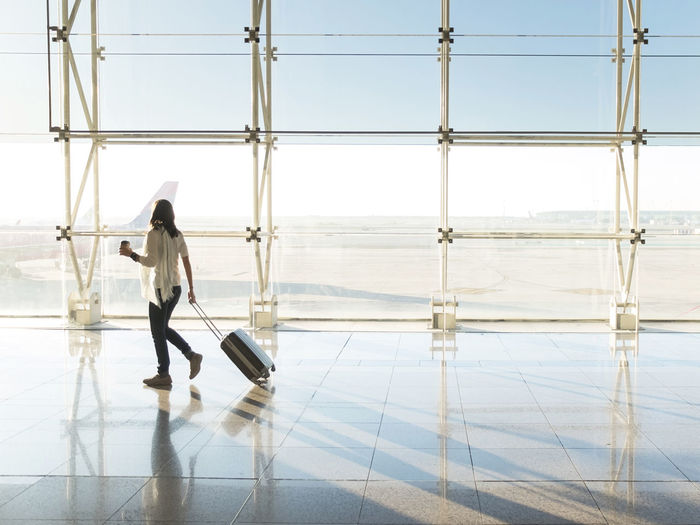 Side view of person on glass window at airport