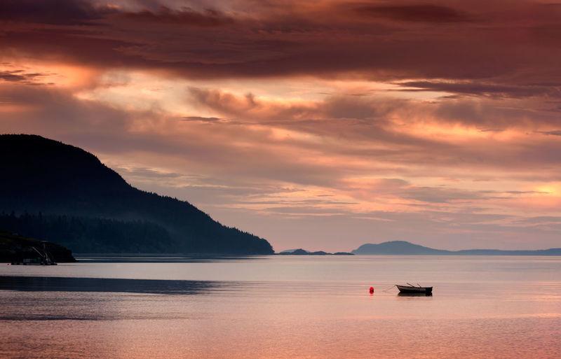 Lone boat in calm lake against scenic sky