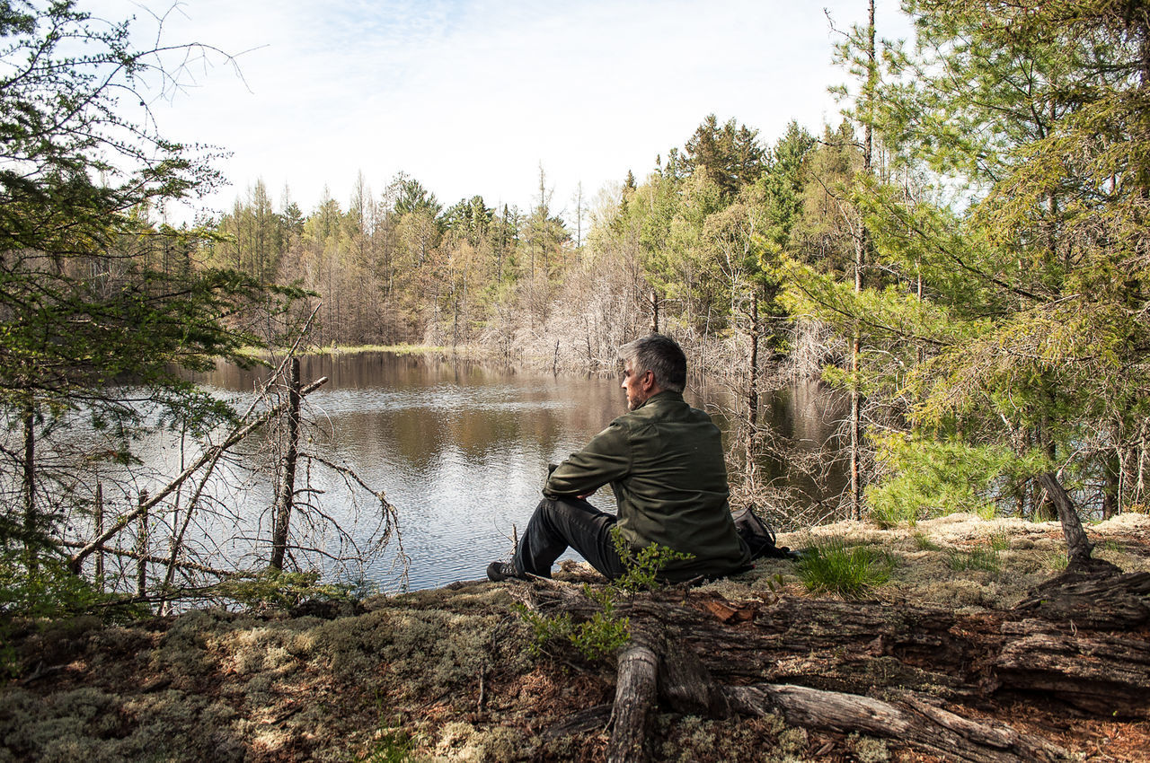 WOMAN SITTING BY RIVER IN FOREST