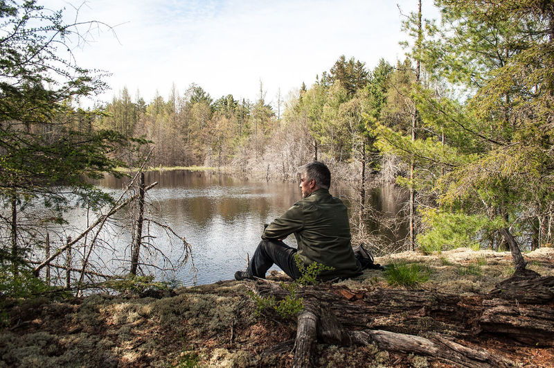Man sitting by river in forest