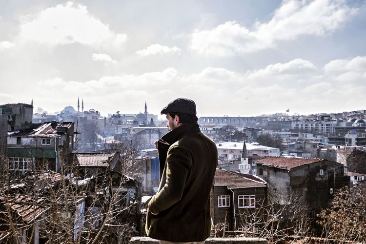 Rear view of man with cityscape in background
