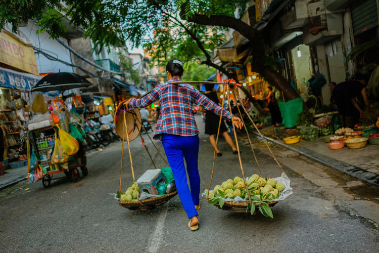 Rear view of man having food in market
