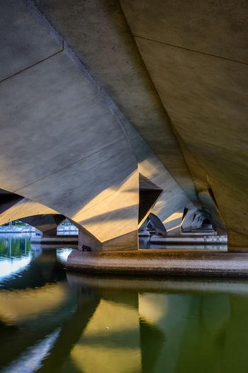 Bridge over lake against buildings
