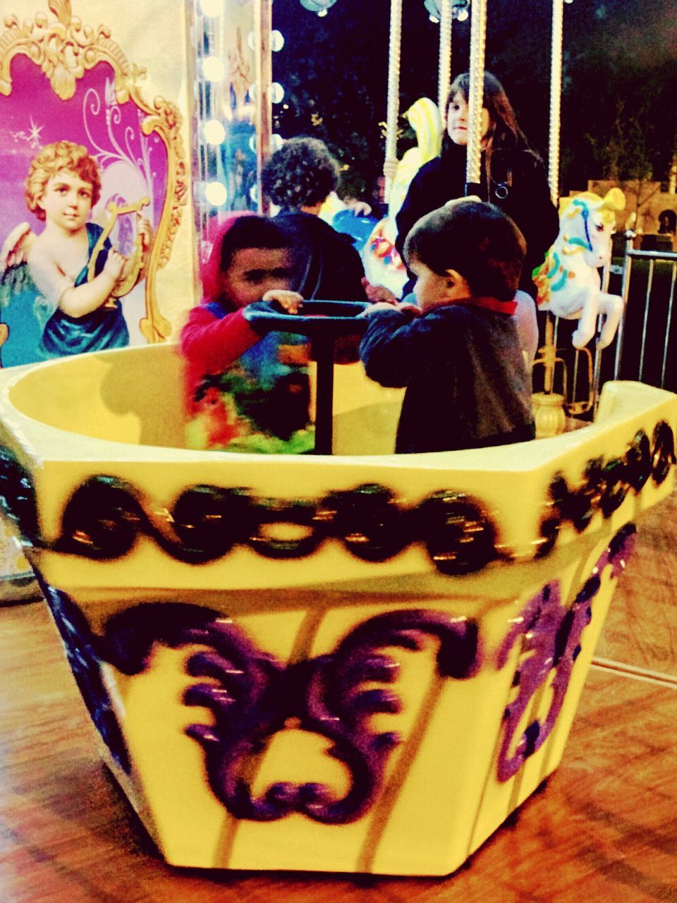childhood, real people, leisure activity, boys, amusement park, lifestyles, two people, fun, full length, enjoyment, girls, indoors, sitting, day, togetherness, carousel, close-up, people