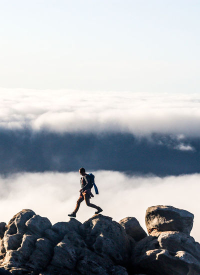 Hiker walking across rock boulders with scenic cloud formation in the background Adventure Balance Cloud - Sky Day Fitness Full Length Hike Hiker Hiking Landscape Landscape_Collection Leisure Activity Male Mountain Nature One Person Outdoor Photography Outdoors Rock - Object Tranquility Walk Walking Wilderness Young Adult