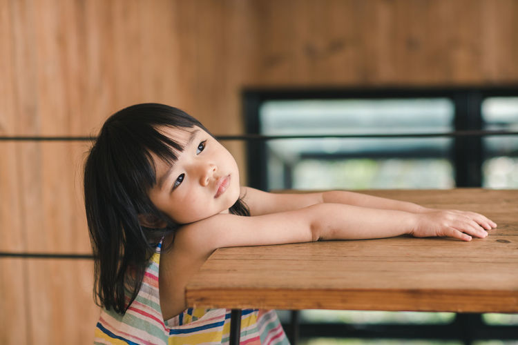 Thoughtful Girl Leaning On Wooden Table