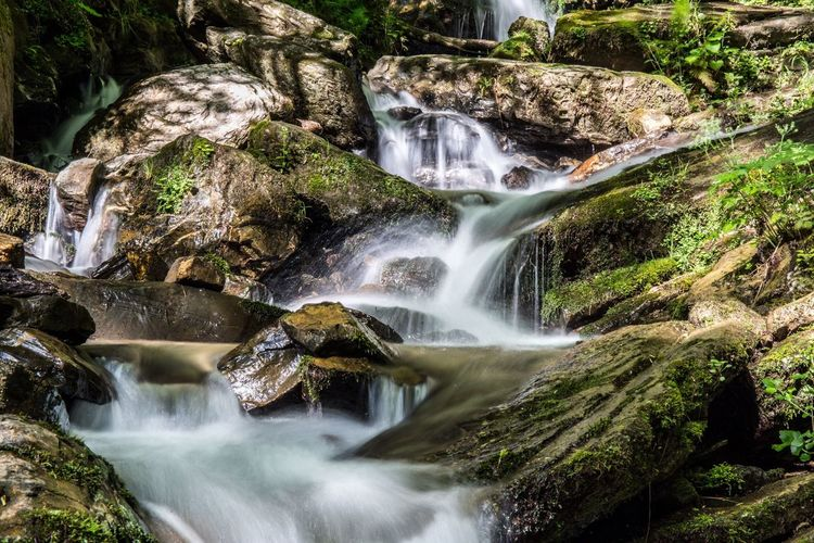 Stream Flowing Through Rocks At Forest