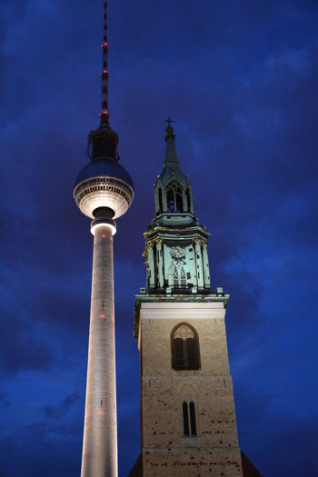 Low Angle View Of Fernsehturm And St Mary Church Against Sky At Dusk
