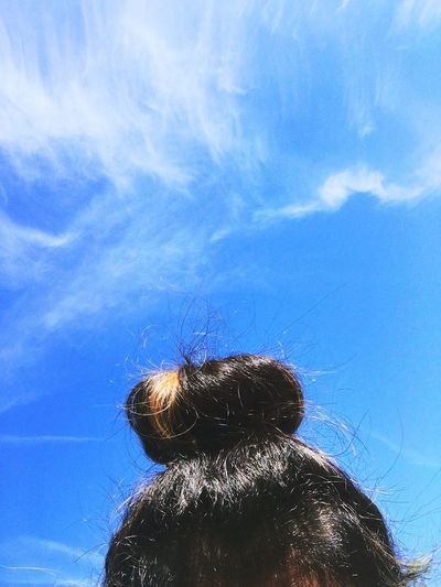 Rear view of girl against blue sky