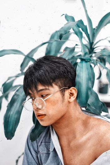 Close-Up Of Young Man Wearing Eyeglasses Against Plants