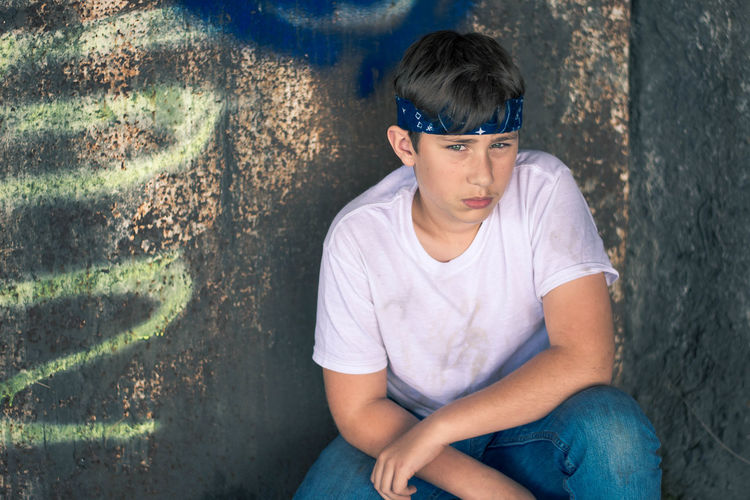 Portrait of young man sitting against wall
