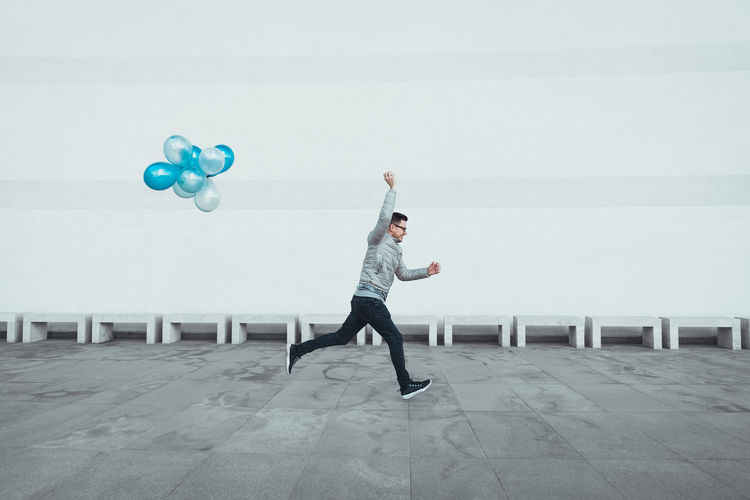 Full length of young man running with balloons