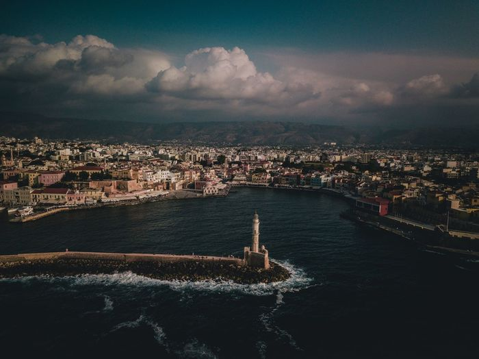 Aerial View Of Cityscape By Sea Against Cloudy Sky During Sunset