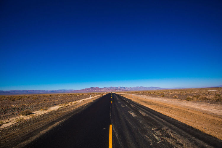 Road amidst landscape against clear blue sky