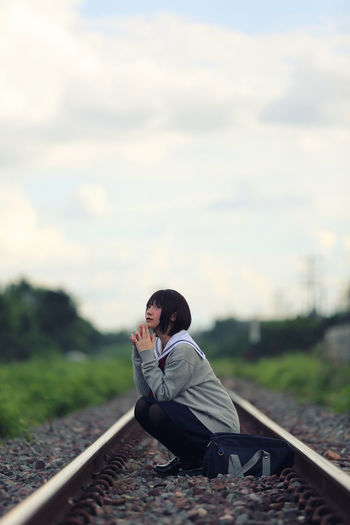 Young woman crouching on railroad track against sky
