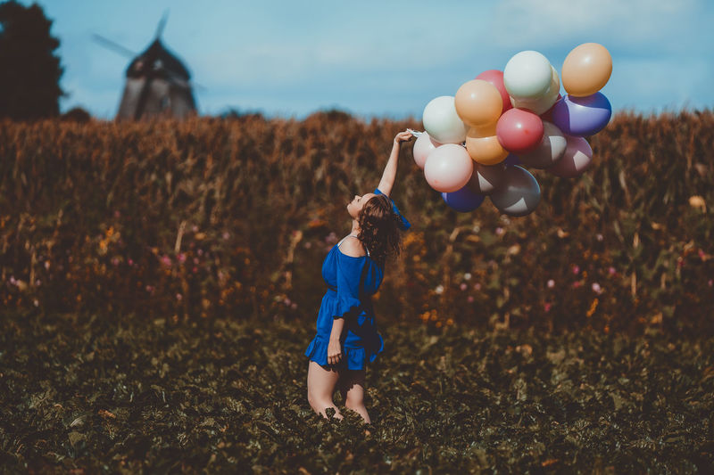 Woman holding balloons while standing by plants