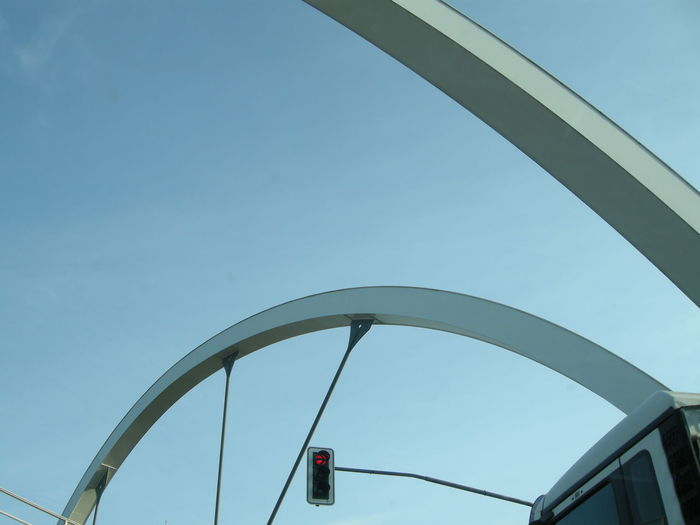 Cropped image of bus on arch bridge by road signal against clear sky