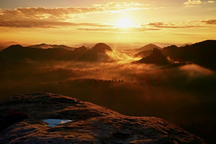 View into long deep valley full of heavy colorful mist. autumn landscape within daybreak after rain