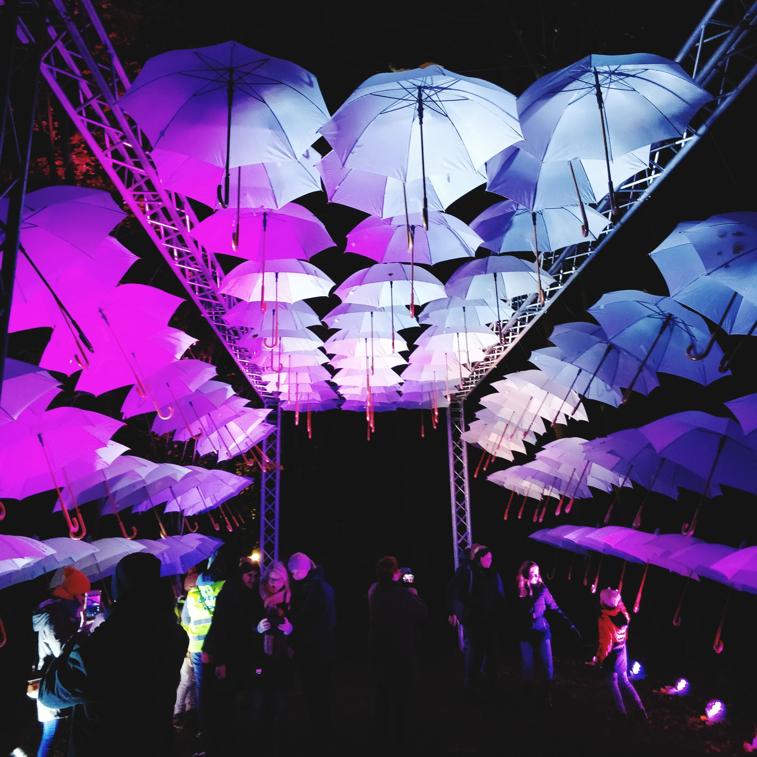 group of people, real people, umbrella, men, protection, large group of people, women, night, crowd, lifestyles, illuminated, adult, leisure activity, group, architecture, decoration, outdoors, built structure