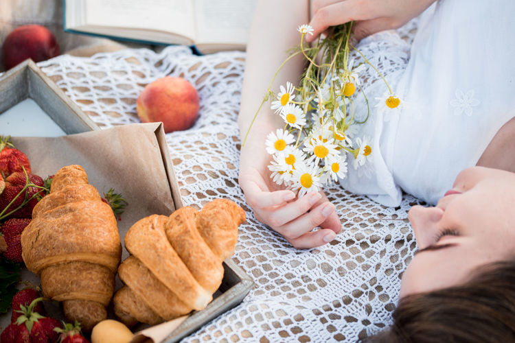 High angle view of woman holing flowers lying on bed with food