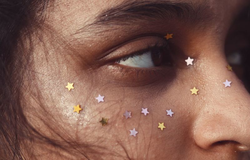 Close-up of woman with star shape decoration on face
