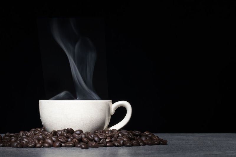 Cup of coffee with coffee bean on black background Coffee - Drink Coffee Black Background Mug Roasted Coffee Bean Coffee Cup Food And Drink Indoors  Cup Studio Shot Drink Copy Space Smoke - Physical Structure Steam No People Heat - Temperature Food Table Close-up Freshness Hot Drink Caffeine Crockery Tea Cup