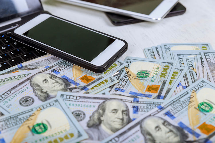 High angle view of technologies with paper currency on desk