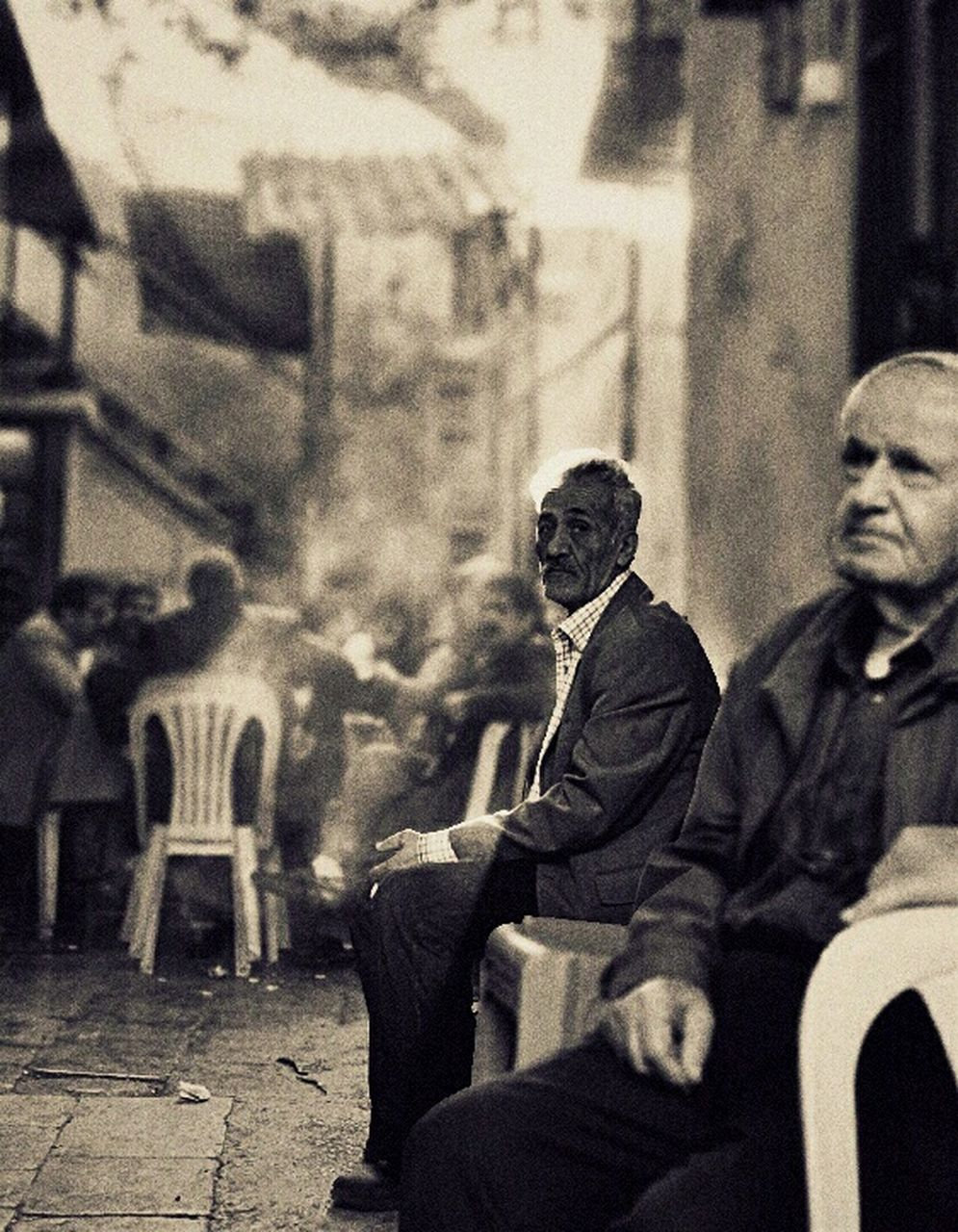 sitting, men, real people, two people, city, adult, outdoors, building exterior, day, people, only men, adults only