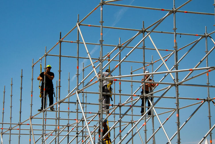 People working at construction site against clear blue sky