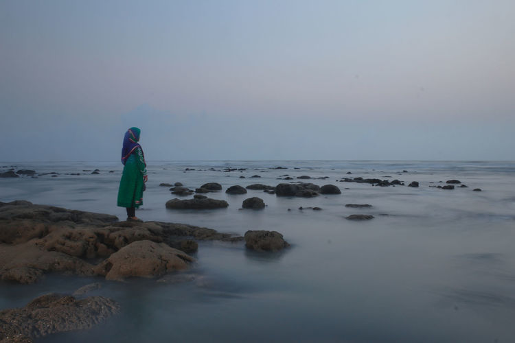 Rear view of woman standing on rock by sea against clear sky
