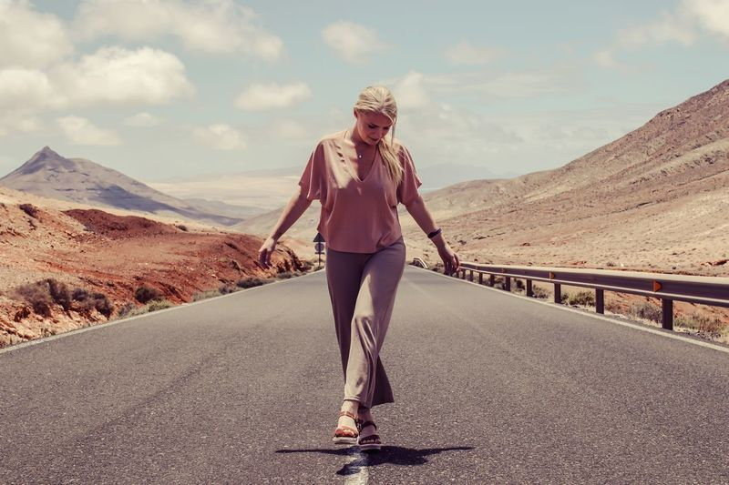 Full length portrait of woman standing on road against sky