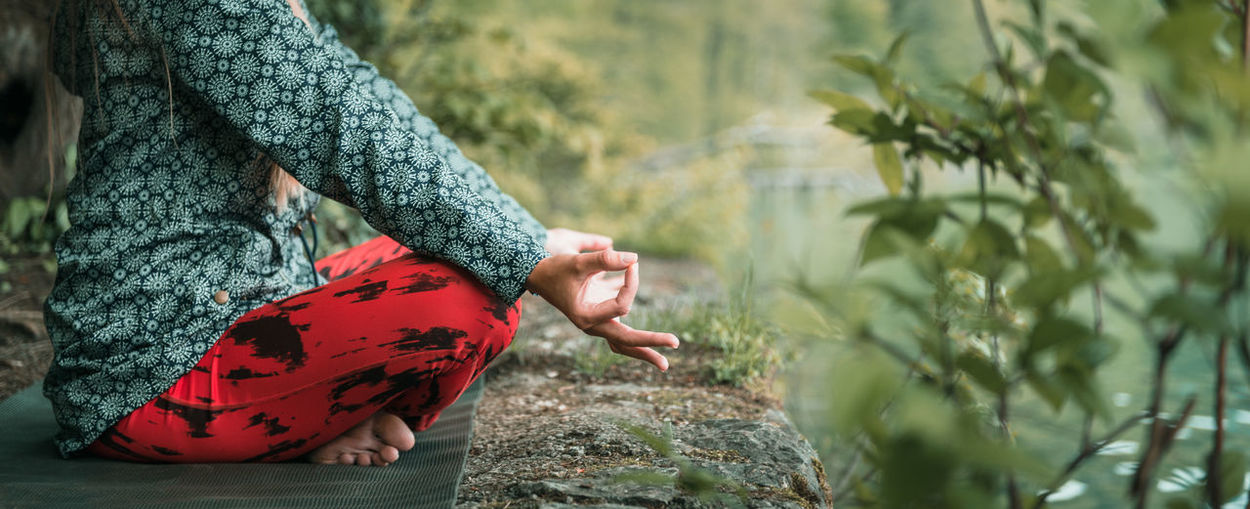 Low section of woman doing yoga on rock