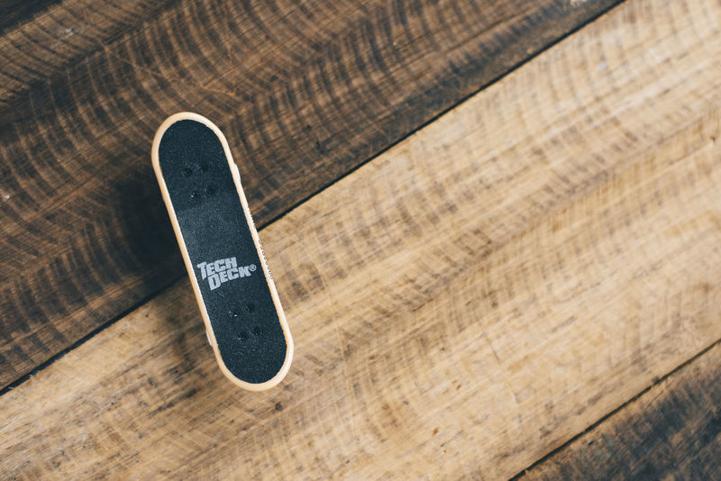 Tech Deck brand finger skateboard put on a wooden table background Children Lifestyle Practice Wheel Young Youth Activity Board Childhood Concept Equipment Finger Game Hobbies Hobby Leisure Object Skate Skateboard Skateboarder Small Sport Tech Deck Toy Tricks