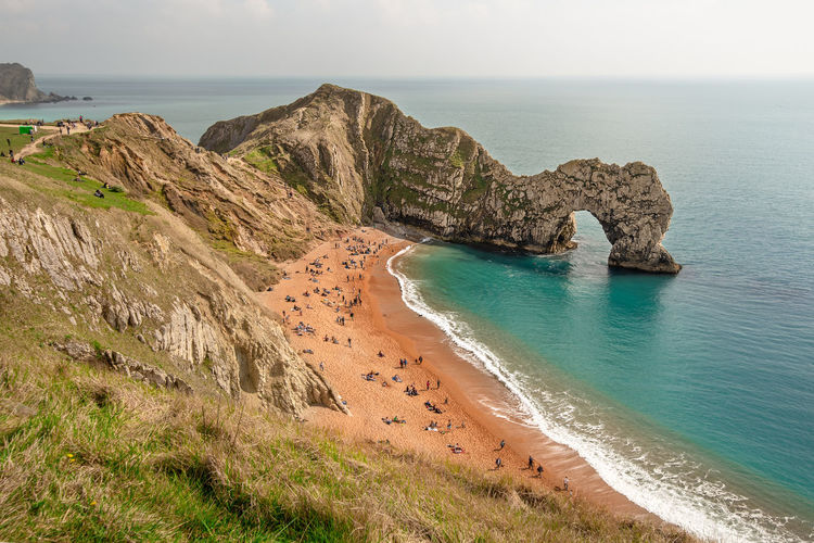 A high up view of the famous limestone arch Durdle Door and golden sand beach from the South West Coastal Path running on top of the near by cliffs, Lulworth Estate, Dorset, England. Durdle Door Jurrasic Coast Arch Beach Beauty In Nature Cliff Day Horizon Horizon Over Water Idyllic Land Natural Arch Nature No People Outdoors Rock Rock - Object Rock Formation Scenics - Nature Sea Sky Solid Tranquil Scene Tranquility Water