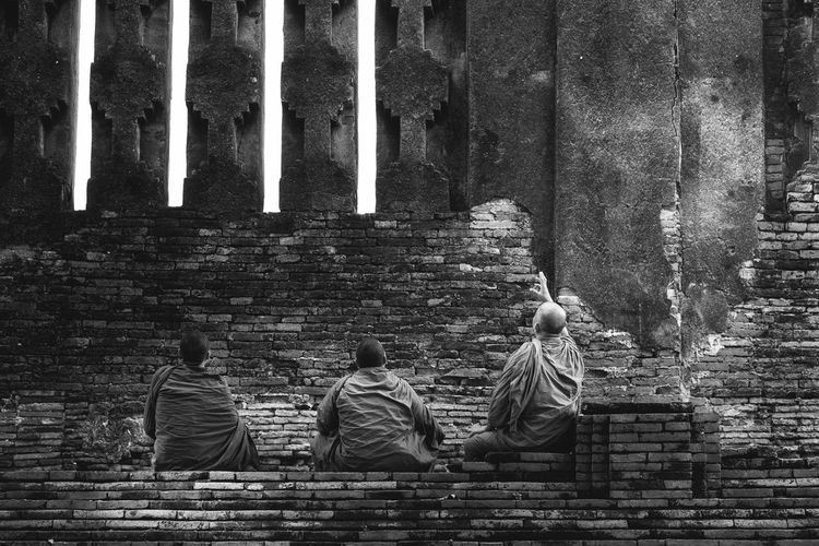 Rear view of monks sitting at buddhist temple