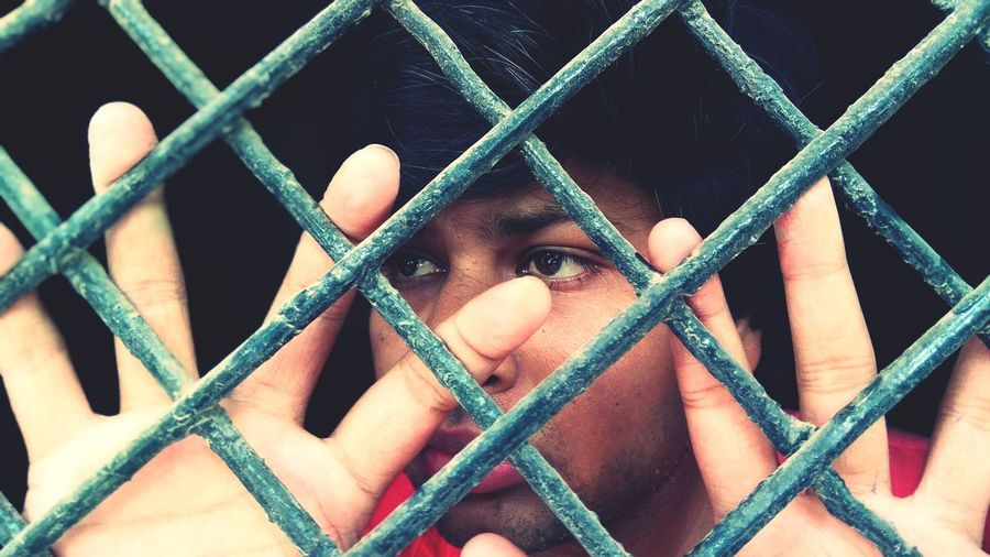 Portrait of man seen through fence