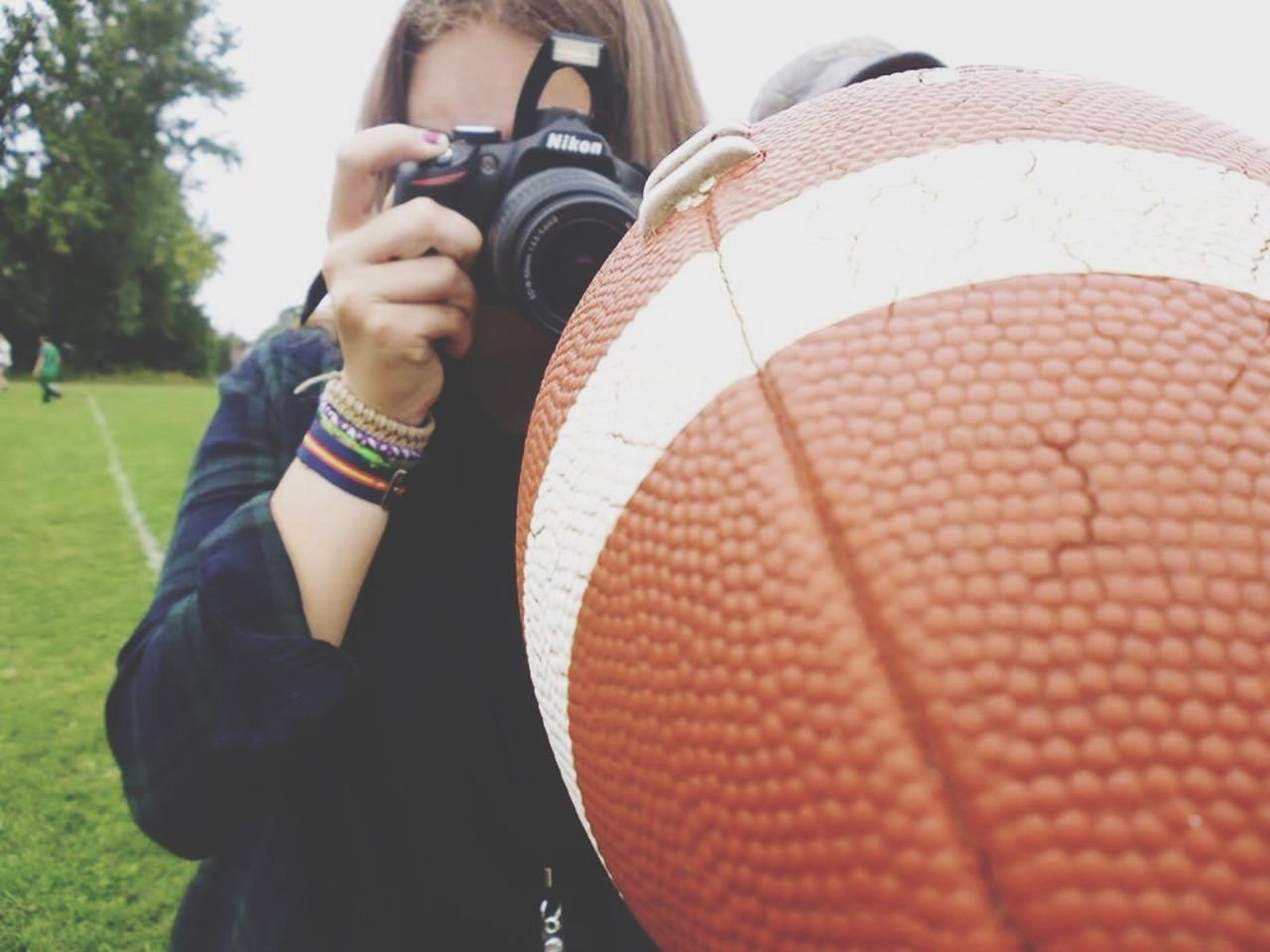 real people, leisure activity, one person, lifestyles, holding, day, photographing, outdoors, photography themes, ball, playing, sport, technology, women, young women, camera - photographic equipment, basketball - sport, young adult, close-up, adult, people