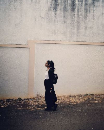 Side view of woman looking away against wall