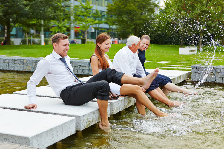 Business people enjoying in pond at park