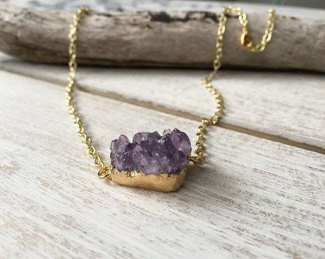 Close-up of amethyst with gold necklace on table