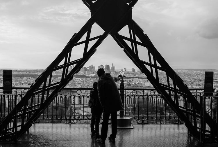 Man And Child Standing In Eiffel Tower Against Sky In City