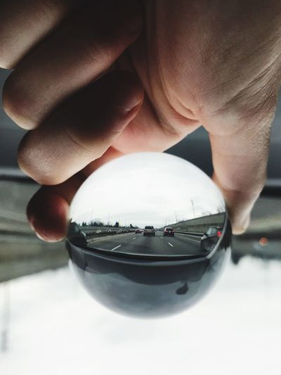 Cropped hand holding crystal ball against road