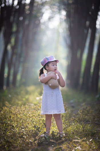 Casual Clothing Childhood Day Focus On Foreground Forest Full Length Girls Grass Leisure Activity Lifestyles Nature One Person Outdoors People Real People Standing Tree Tree Trunk