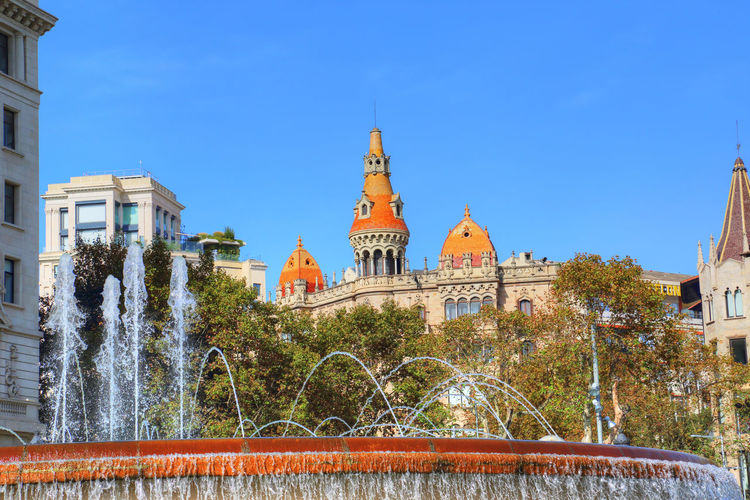 Barcelona buildings facing Catalunya Square Barcelona, Spain Spaın Barcelona Plaza De Catalunya Plaza De Cataluña Central Plaza Las Ramblas Center Destination Attraction Tourism Sunset Beaitiful Fountain Architecture Domestic Animals Streets