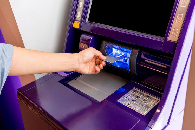 Hand of Asian woman inserting ATM card into purple ATM machine. Economy Electric Machine Screen Atm Card Cash Computer Credit Credit Card Digits Exchange Finance System