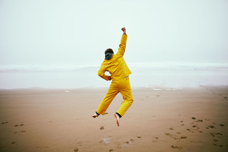 Rear view of man jumping at beach against clear sky